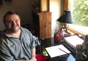 Marcus, and adult with Down syndrome, sitting and smiling beside a desk with a notebook and pencil